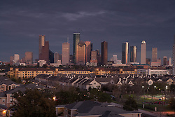 Houston, Texas skyline at sunset from the west with residential neighborhood in the foreground.