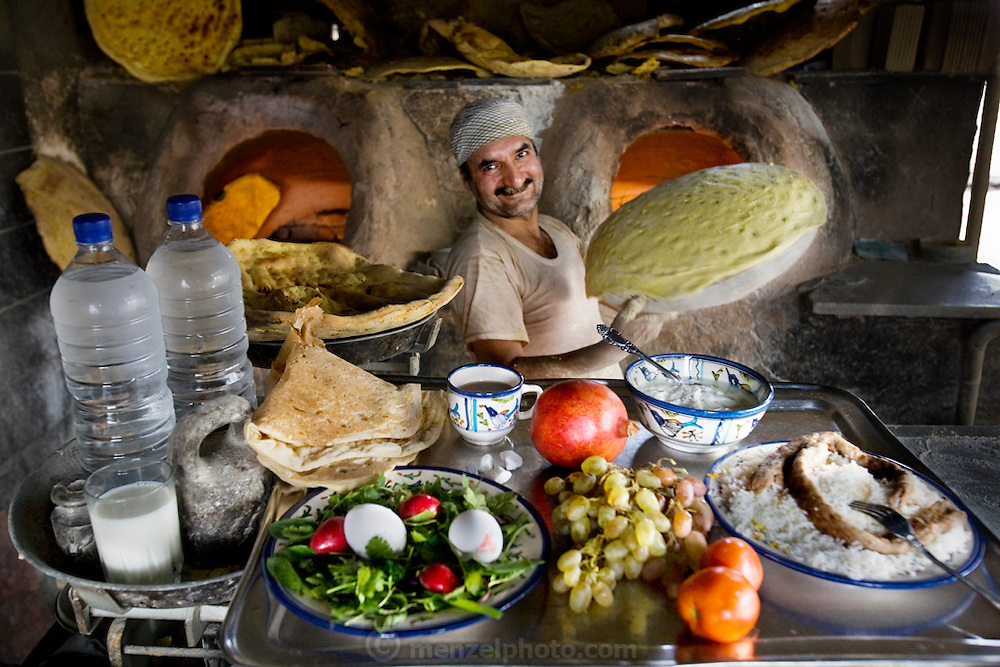 Akbar Zareh with his typical day's worth of food at his bakery in the province of Yazd, Iran. (From the book What I Eat: Around the World in 80 Diets.) MODEL RELEASED.