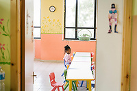 "SUTERA, ITALY - 8 JANUARY 2018: The daughter of  Nigerian asylum seekers attends is seen here in a kindergarten class in Sutera, Italy, on January 8th 2018.<br /> <br /> Sutera is an ancient town plastered onto the side of an enormous monolithic rock, topped with a convent, in the middle of the western half of Sicily, about 90 minutes by car south of the Sicilian capital Palermo<br /> Its population fell from 5,000 in 1970 to 1,500 today. In the past 3 years its population has surged  after the local mayor agreed to take in some of the thousands of migrants that have made the dangerous journey from Africa to the Sicily.<br /> <br /> ""Sutera was disappearing,"" says mayor Giuseppe Grizzanti. ""Italians, bound for Germany or England, packed up and left their homes empty. The deaths of inhabitants greatly outnumbered births. Now, thanks to the refugees, we have a chance to revive the city.""<br />  Through an Italian state-funded project called SPRAR (Protection System for Refugees and Asylum Seekers), which in turn is co-funded by the European Union's Fund for the Integration of non-EU Immigrants, Sutera was given financial and resettlement assistance that was co-ordinated by a local non-profit organization called Girasoli (Sunflowers). Girasoli organizes everything from housing and medical care to Italian lessons and psychological counselling for the new settlers.<br /> The school appears to have been the biggest beneficiary of the refugees' arrival, which was kept open thanks to the migrants.<br /> Nunzio Vittarello, the coordinator of the E.U. project working for the NGO ""I Girasoli"" says that there are 50 families in Sutera at the moment."