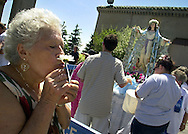 "ATLANTIC CITY, NJ - AUGUST 15:  Rose Agovino, 69, of Philadelphia, Pennsylvania, kisses a mass card and a flower, while saying a prayer, during the Wedding and Blessing of the Sea ceremony, Aug. 15, 2002, in Atlantic City, New Jersey. The ceremony, held in celebration of Feast of the Assumption of the Blessed Mother and the annual ""Wedding and Blessing of the Sea,'' symbolizes the union of the Atlantic Ocean with the resort. This is the 35th consecutive year that the event has been held. (Photo by William Thomas Cain/Getty Images)"