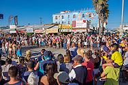 A crowd of spectators gather on the Venice boardwalk - Los Angeles, California.