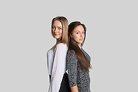 Portrait of female friends standing back to back over white background