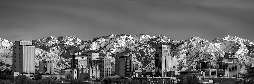 The Salt Lake City skyline in black and white on a late Winter evening as the sun sets.  The Salt Lake City skyline has a magnificent backdrop of the Wasatch Mountains.