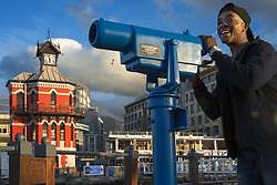 September 30, 2018 - South Africa - A tourist looking through tourist telescope the waterfront of Cape Town. Historic Clock Tower and Tide Gauge Victoria and Albert Waterfront Cape Town South Africa (Credit Image: © Sergi Reboredo/ZUMA Wire)