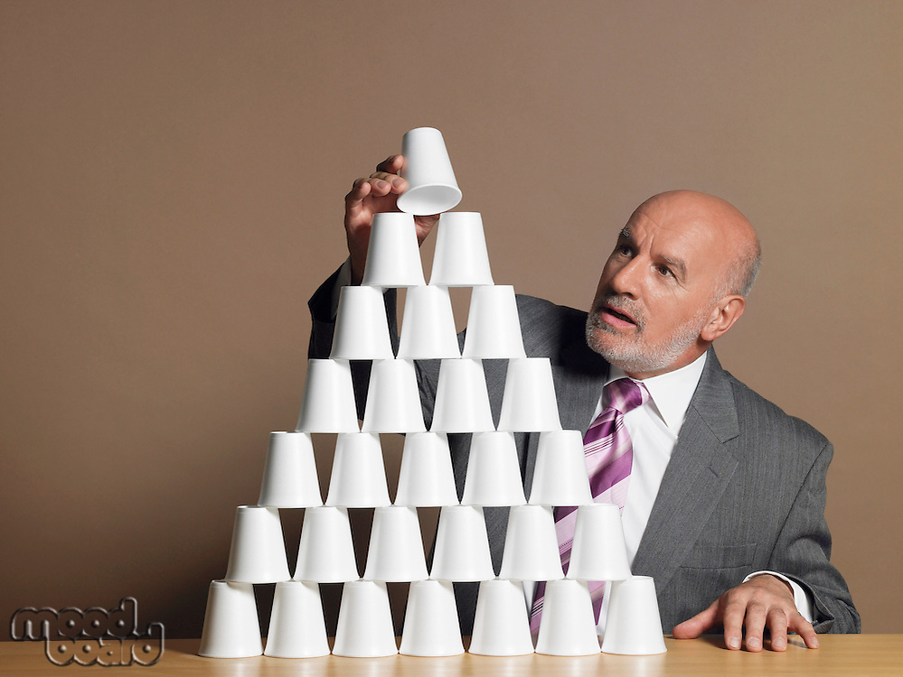 Businessman Building Pyramid of Cups on table