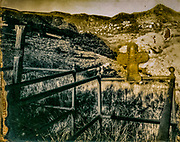 Symbolic corrosion in photo of grave site with ghost town in background