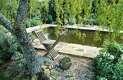 Seat in the shade of a weeping willow by the formal pond. Design: Helen Yemm