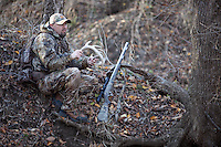 DEER HUNTER WEARING REALTREE AP CAMOUFLAGE RATTLING WITH DEER ANTLERS WHILE A THOMPSON CENTER OMEGA MUZZLELOADER LIES BESIDE HIM