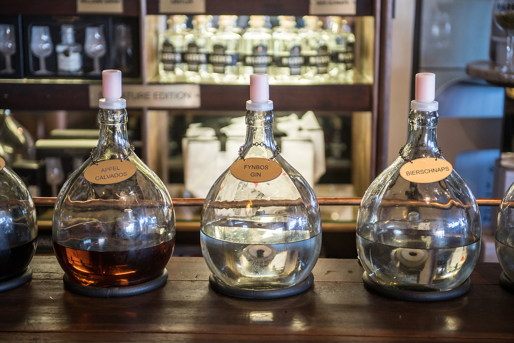 Three bottles of handcrafted distilled spirits in a row on bar top, Cape Town, South Africa