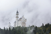 GERMANY, Fussen.  16.08.15 The Neuschwanstein Castle sits characteristically amongst fairy-tale like mist this afternoon. The miraculous building, built in 1886 for the eccentric Bavarian King Ludwig II, has been the inspiration for countless models, book illustrations and film sets. Rick Findler / Story Picture Agency