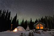 Kenji Yoshikawa in front of his igloo at his reindeer farm outside Fairbanks. Northern lights and stars light up the sky.<br /> Alaska, USA