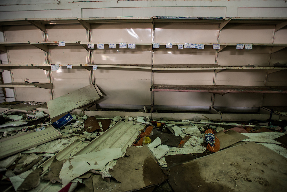 CUMANÁ, VENEZUELA - JUNE 16, 2016: Empty shelves at a grocery store that was destroyed last Tuesday by hundreds of looters in Cumaná, Venezuela. They made it through the doors before the owners could close them, forced a large metal gate open so those outside could pour inside. They took water, flour, corn meal, salt, sugar, potatoes, cereal—leaving behind only a broken freezers and overturned shelves. And they proved that even in country with the richest oil reserves in the world, it was possible for people to riot because there was no food. Venezuela is convulsing from a raft of violence triggered by hunger. It is latest chapter of an economic collapse which has left the country neither able to produce its food nor import it from abroad, leaving a nation searching for how to feed itself. In the past 11 days, scores of businesses, mostly stores, have been looted or destroyed and five people have died in the confrontations. With delivery trucks under constant attack, the nation's food is now transported under armed guard. Entire cities have been militarized under an emergency decree from President Nicolás Maduro; bakeries are now watched over by the National Guard.  PHOTO: Meridith Kohut for The New York Times
