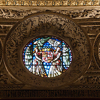 Detailed relief surrounds a stained glass window in the Alcazar of Segovia, Spain.