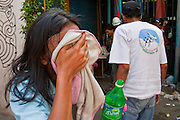 14 MAY 2010 - BANGKOK, THAILAND: Thais try to wipe tear gas from their eyes after Thai troops fired several gas grenades into a crowd of anti-government protesters on Rama IV Road Friday afternoon. Thai troops and anti government protesters clashed on Rama IV Road Friday afternoon in a series of running battles. Troops fired into the air and at protesters after protesters attacked the troops with rocket and small homemade explosives. Unlike similar confrontations in Bangkok, these protesters were not Red Shirts. Most of the protesters were residents of nearby Khlong Toei slum area, Bangkok's largest slum area. The running battle went on for at least two hours.   PHOTO BY JACK KURTZ
