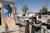 Helmand Province, Lashkargah City..Locals watching the picture of the Afghan bodybuilder champion Mr Ustad Aziz Nikyar.