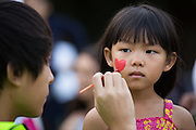 Rachel Sie, 4, of San Jose has a heart painted on her cheek during the National Night Out event at Berryessa Creek Park in San Jose, California, on August 5, 2014. (Stan Olszewski/SOSKIphoto)