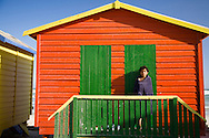 A young boy, wrapped in a towel, stands on the front porch of a beach house at Muizenburg, South Africa