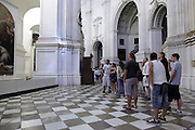 group of teenagers inside the Cathedral in Granada Spain looking at a painting