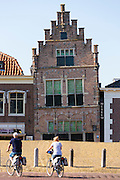 Cyclists and traditional architecture lopsided ancient building of theTown Hall Museum, Edam, The Netherlands