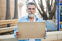 Portrait of smiling homeless person with sign