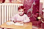staged classroom portrait of a young boy drawing ca1960s