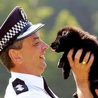 Inspector Alan Davies of Strathclyde Police Dog Branch shows off a German Shepherd puppy from litter E which is to be named in a competition.
