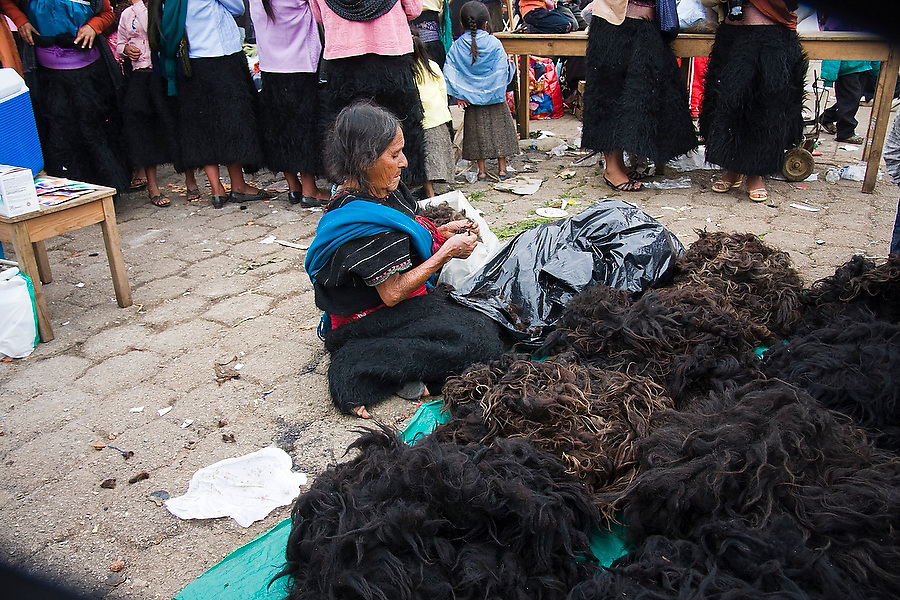 An elderly woman sells mounds of black sheep wool, from which their traditional skirts are made, during the festival for San Juan Bautista in the Tzotzil Mayan village of San Juan Chamula, outside of San Cristobal de las Casas, Chiapas state, Mexico on June 24, 2008.