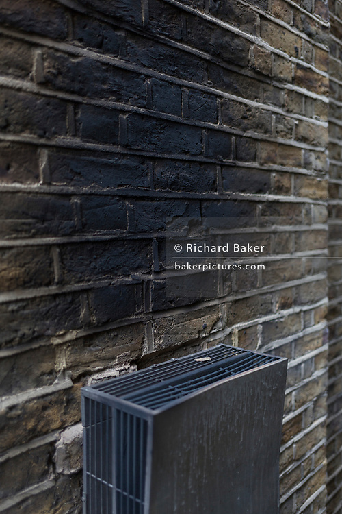 Sooted and scorched brick wall of a house, blackened because of a faulty boiler, on 17th March 2017, in south London, England.