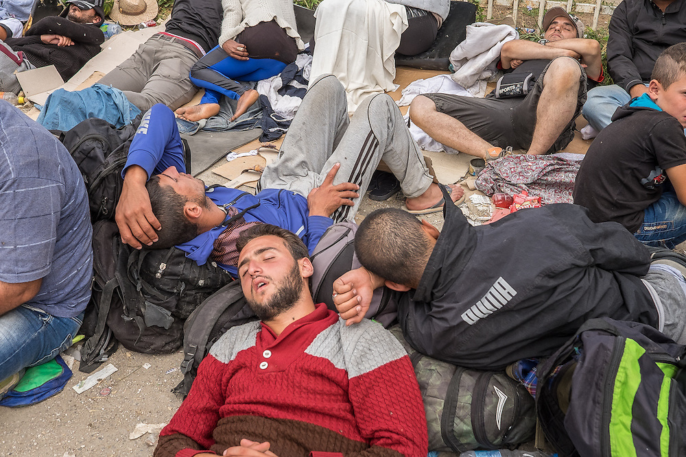 "Refugees from Syria rest while awaiting admission to a ""one stop"" camp set up by the Serbian Commissariat for Refugees and Migration in the town of Presevo, near the the country's border with Macedonia."