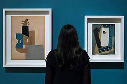 "© Licensed to London News Pictures. 21/01/2020. LONDON, UK. A staff member views (L to R) ""Violin"", 1912, and ""Guitar"", 1913, both by Pablo Picasso at the preview of ""Picasso and Paper"", an exhibition at the Royal Academy of Arts, which is the most comprehensive exhibition ever devoted to Pablo Picasso's imaginative and original uses of paper .  Over 300 works both on and with paper, are on display 25 January to 13 April 2020.  Photo credit: Stephen Chung/LNP"