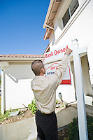 Young man putting up 'for sale notice'