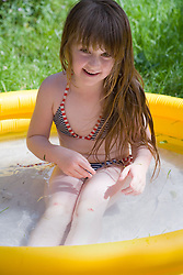 Little girl playing in a paddling pool,