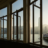 China, Hong Kong, View through windows of Kowloon Star Ferry Terminal with approaching ferry and city skyline in background at sunset