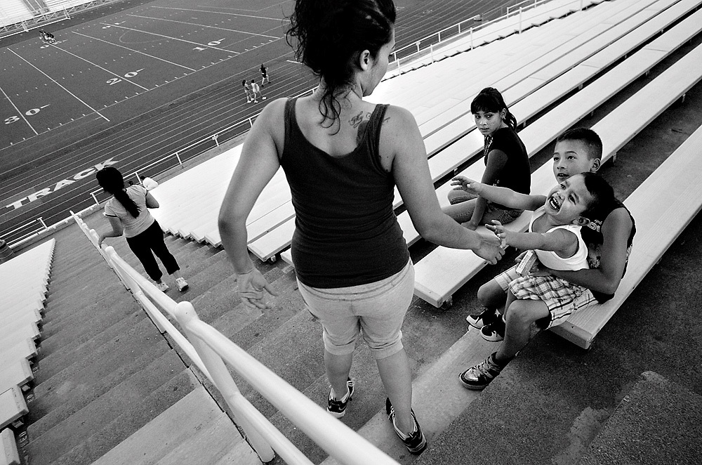 Chris Espinoza, 1, of Kennewick, cries and reaches for his mother Martha Chavez Thursday evening while she ran stair laps with her friend Amparo Valencia, left, of Pasco, at Edgar Brown Memorial Stadium in Pasco. Her other children, Memo, right, 10, and Cynthia Contreras, 11, took turns watching Espinoza while exercising. Chavez says they alternate between Edgar Brown and Lampson Stadium in Kennewick.