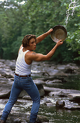 sexy man in a stream throwing water with a pan