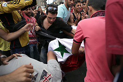 © Licensed to London News Pictures. Budapest, Hungary. Frustrated Syrian refugees fight amongst themselves, when an Assadite migrant brings an official Syrian flag to the Keleti station in Hungary. Some of the refugees boarded trains which took them to a temporary camp along the train line in Bicske. Photo credit: Gabriel Szabo/LNP