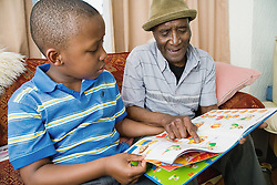 Grandfather and grandson reading a book together at home,
