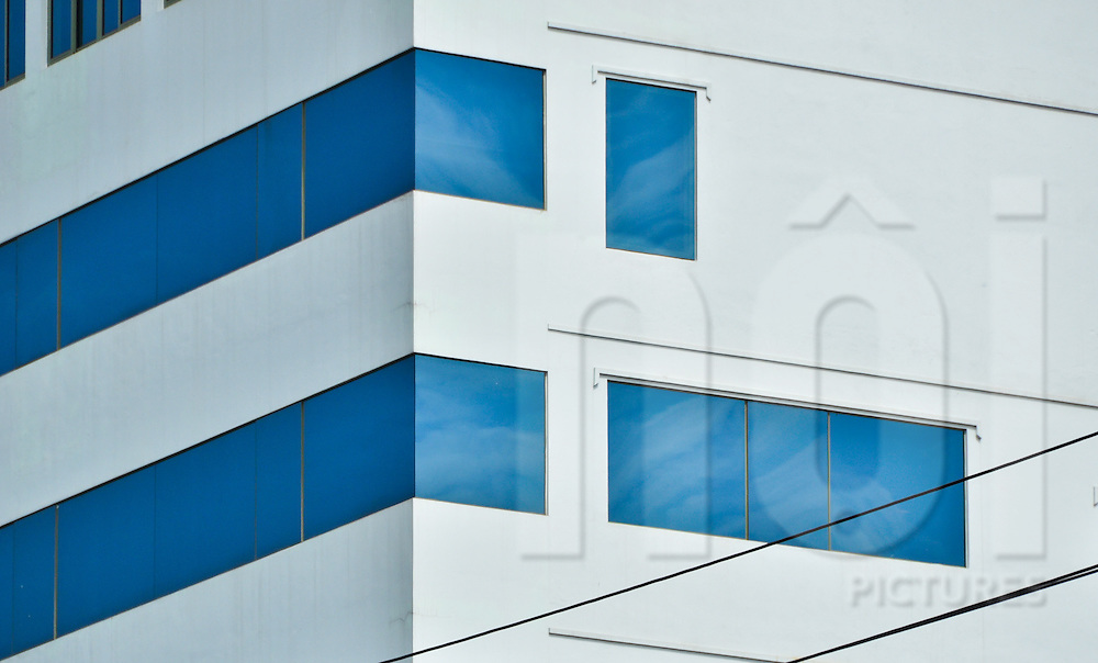 Glass windows of a modern building on Hoang Quoc Viet street reflect the blue sky, Cau Giay district, Hanoi, Vietnam, Southeast Asia