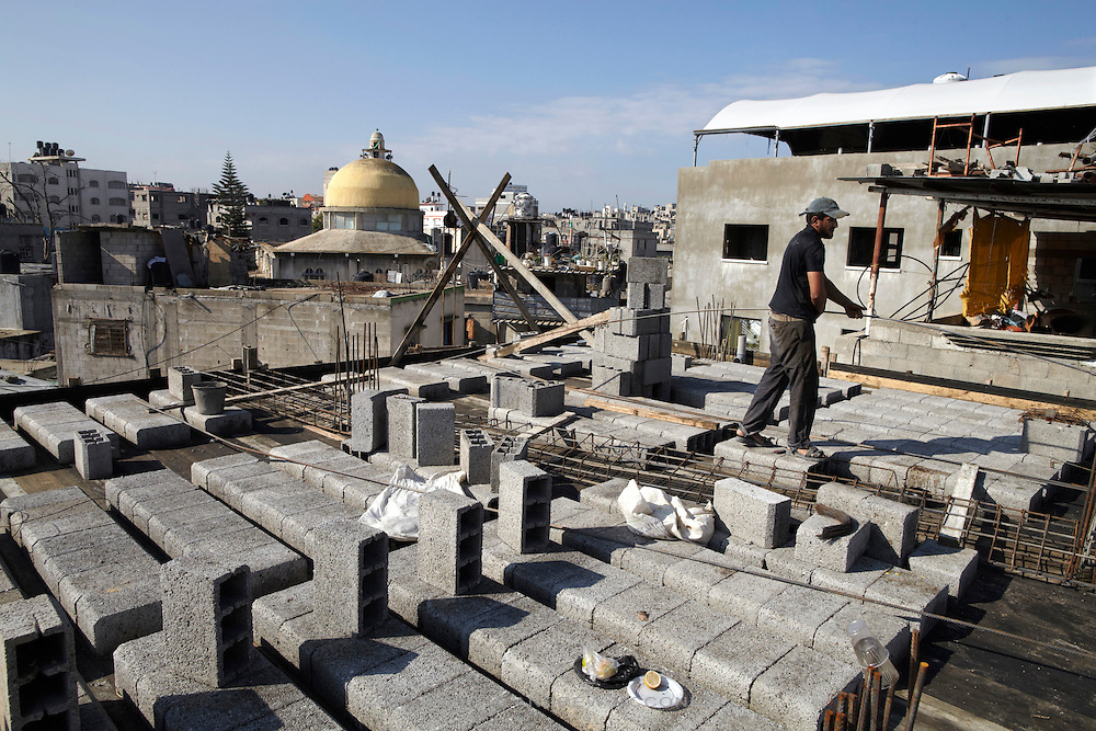 A labourer sets out concrete blocks on a rooftop in preparation for concrete to be poured, in Jabaliya, Gaza.