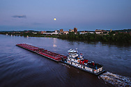 The moon rises above the river front park in Huntington, West Virginia with a large boat passing through the Ohio River.