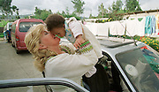 8/8/01 -- (PHOTO BY MIKE FENDER) w/ story, slug: AFRICA, file: 62040 // Cheryl Carter-Shotts gives Beza, 11 months, a kiss before a caravan leaves the Americans for African Adoption foster home for the airport in Addis Ababa. Beza was one of six children coming to new homes and families in America. Beza joined a family in Bloomington along with another girl from the home.