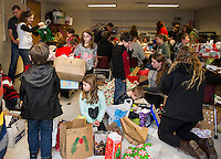 It was a flurry of activity in the wrapping room during the Presents for Pleasant event as Laconia High School and Pleasant Street Elementary School students shopped and wrapped Friday evening.  (Karen Bobotas/for the Laconia Daily Sun)