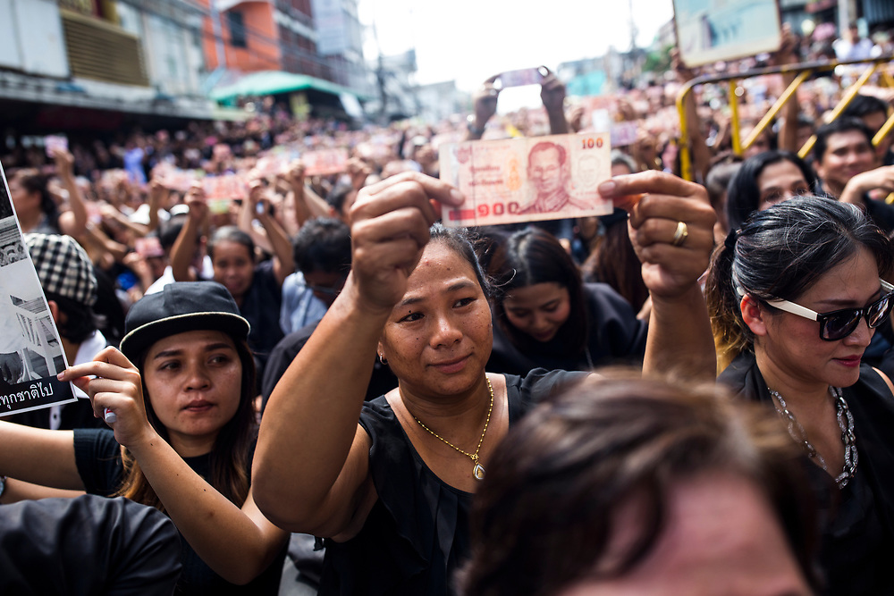 Crowds hold up baht notes with a portrait of King Bhumibol outside of Siriraj Hospital on June 14, 2016 in Bangkok, Thailand. Thailand's King Bhumibol Adulyadej, the world's longest-reigning monarch, died at the age of 88 in Bangkok's Siriraj Hospital on Thursday after his 70-year reign. Prime Minister Prayut Chan-ocha made a statement Thailand would hold a one-year mourning period as the Crown Prince Maha Vajiralongkorn confirmed that he would perform his duty as heir to the throne.