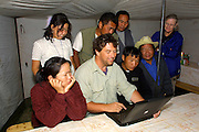 GOBI DESERT, MONGOLIA..09/02/2001.Between Bogd and Bayanhongor. Goodbye party at Nomads Tours camp. Heimo Aga showing digital images of Gobi desert and of themselves to Nomads staff on his Apple PowerBook G3/500..(Photo by Heimo Aga).