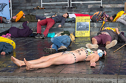"© Licensed to London News Pictures;02/09/2020; Cardiff, Wales, UK. A woman in a swimming costume takes part in a ""drown in"" at an Extinction Rebellion protest in Cardiff Bay in front of the Senedd, the Welsh Government building, in support of the upcoming Climate and Ecological Emergency Bill. She has 1.5m painted on her torso referring to projected rises in sea levels. Today the protest is ""Rising Tide Action!!"" focusing on the impact that the climate crisis is having locally and across Wales because it is impacting weather cycles, flooding, air pollution and our food security. The protest involved arts, theatre, speakers, music, banners and a drown in. The protest is part of a national protest over the next two weeks including London and other cities in the UK against climate change. XR say that despite clear scientific evidence of the deadly climate and ecological emergency, the UK government are refusing to take the urgent action needed to avoid mass extinction, and that politicians need to support the Climate and Ecological Emergency Bill. During the coronavirus covid-19 pandemic, climate change is being forgotten but it is still an emergency that is happening. The protest was socially distanced and participants wore masks. Photo credit: Simon Chapman/LNP."