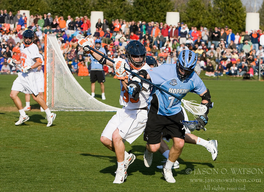 Virginia defenseman Matt Kelly (33) challenges Johns Hopkins attackman Michael Doneger (14). The #2 ranked Virginia Cavaliers defeated the #6 ranked Johns Hopkins Blue Jays 13-12 in overtime at the University of Virginia's Klockner Stadium in Charlottesville, VA on March 22, 2008.  The loss, in front of a record UVA crowd of 7,500, was the third consecutive overtime defeat for Hopkins, the defending national champions.