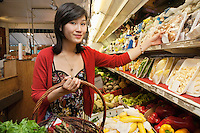 Portrait of young woman choosing mushroom package in market
