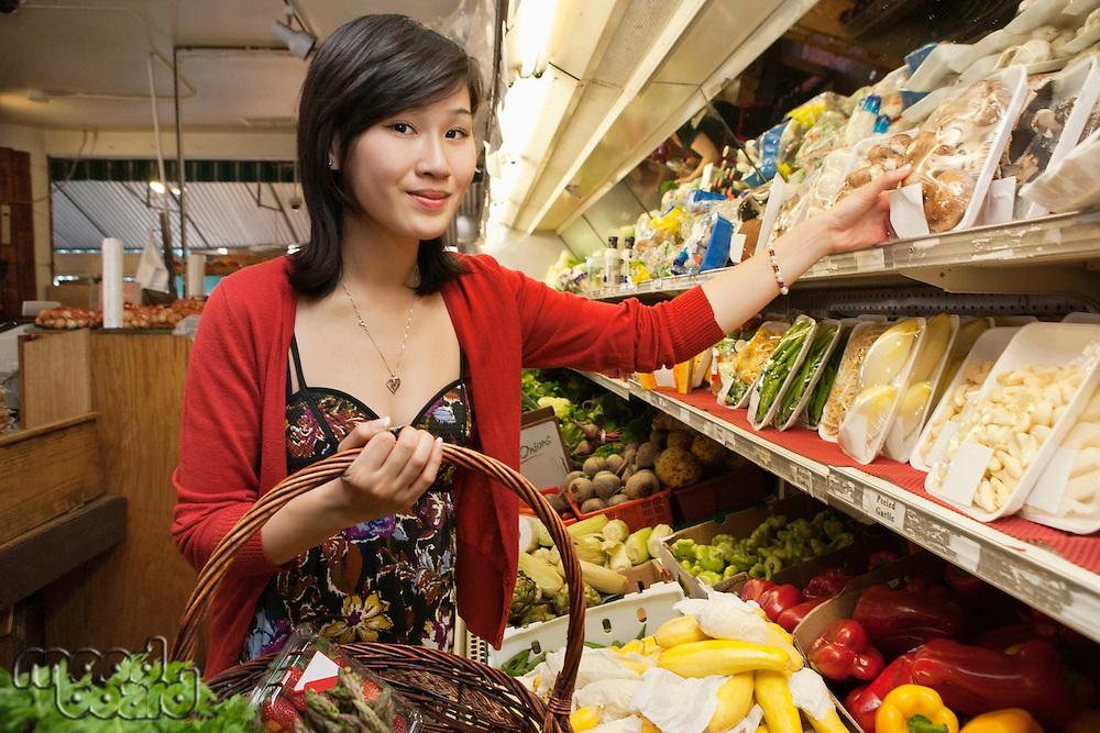 Portrait of young woman choosing mushroom package in market