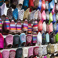 A display of colorful traditional leather shoes at one of the  crowded market stalls in the Medina of Marrakesh, Morocco.