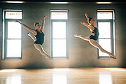 Two ballerinas leaping together